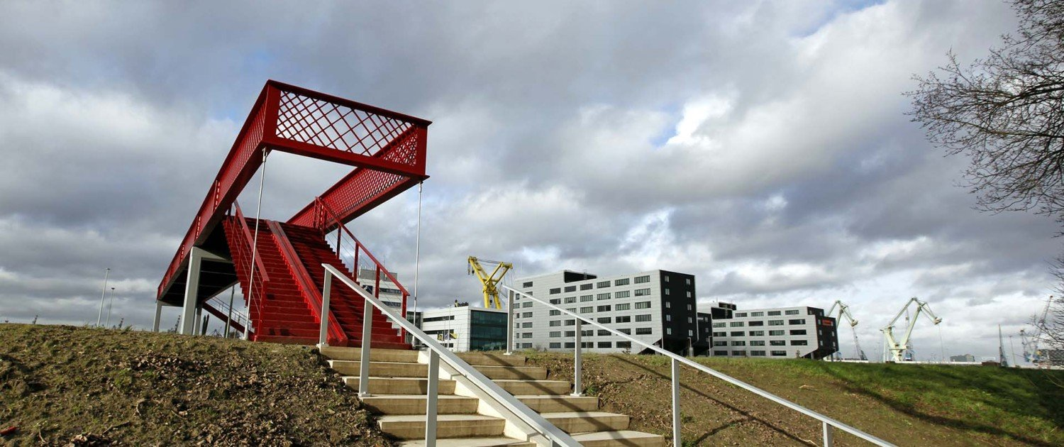 slender, modern, bright red foot and cycle bridge across railway